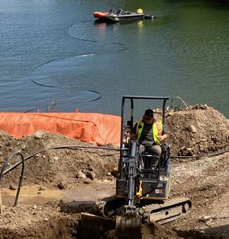 mini excavator being employed at lake side